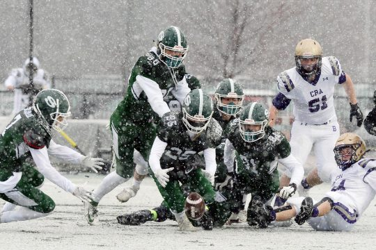 Shenendehowa's Ely Bruhns and Nicholas Mcletchie-Goldman reach for the fumble during their Class AA football game in the snow against CBA at Shenendehowa on Thursday.