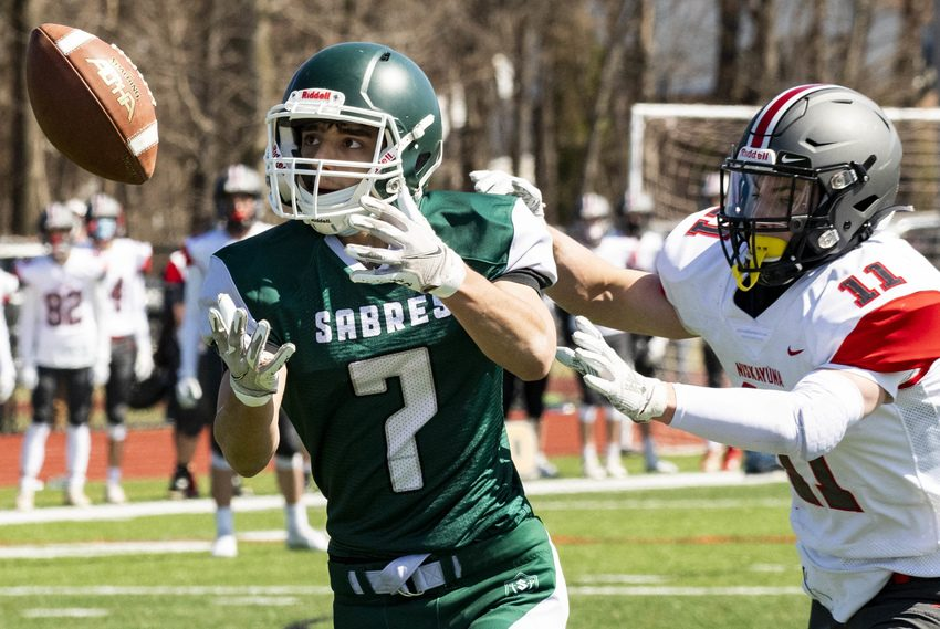 Schalmont's Ethan Coom (7) tries to haul in a pass while pressured by Niskayuna's Dan Quinnon Saturday at Mohonasen High School.