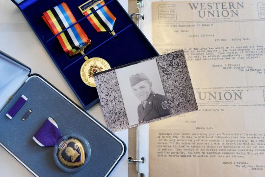 Photograph of late Walter Alvin Smead, surrounded by his Purple Heart and Ambassador for Peace medals and missing in action letters addressed to family members