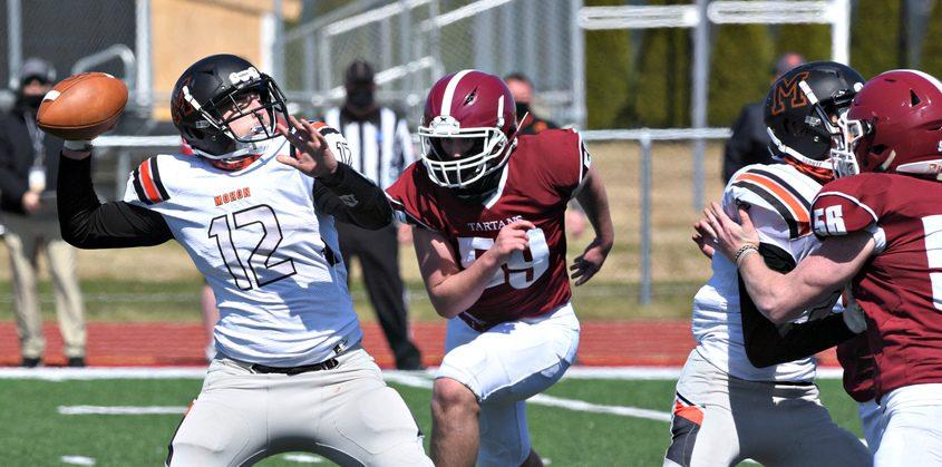 Mohonasen quarterback Tyler Reinke readies his throw as Scotia-Glenville's Brenden Adams bears down on him Saturday afternoon at Scotia-Glenville High School.