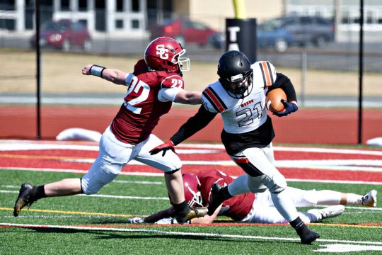 Mohonasen punter Kyle Shendler gets away from Scotia-Glenville defender Paul Marotta after a dropped snap deep in Warriors territory on Saturday, April 3 at Scotia-Glenville High School.