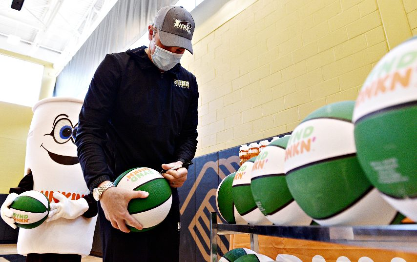 Siena head coach Carmen Maciariello signs basketballs forkids while visiting Adeline Wright Graham Boys and Girls Club in Schenectady on Monday.Dunkin' franchisees donated water bottles and basketballs.