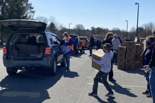 Volunteers load food and personal care items onto vehicles at the mass food distribution event at the Johnstown Junior-Senior High School Monday.