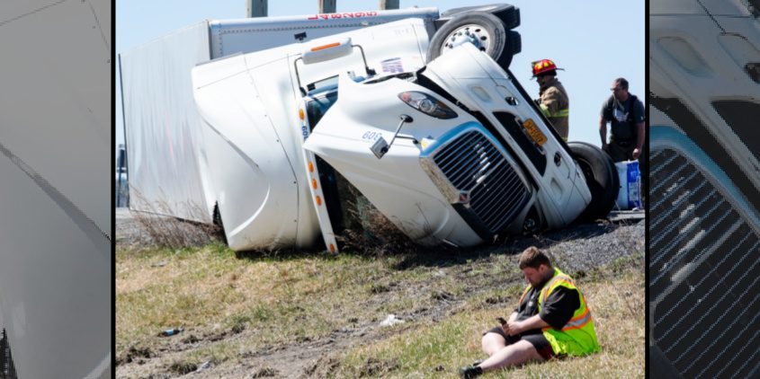 The driver of the overturned tractor-trailer tooks at his cell phone after escaping injury in the noontime crash