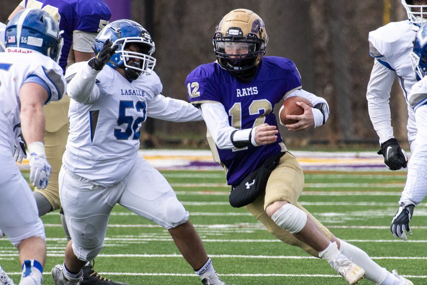 Amsterdam quarterback Tommy Ziskin scrambles upfield with La Salle's Dev Patel in pursuit during a Friday, April 2 game at Lynch Literacy Academy in Amsterdam.