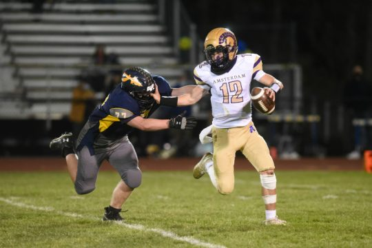 Amsterdam quarterback Tommy Ziskin gets away from Averill Park's Tyler Spink late in the fourth quarter Friday night. April 9, 2021
