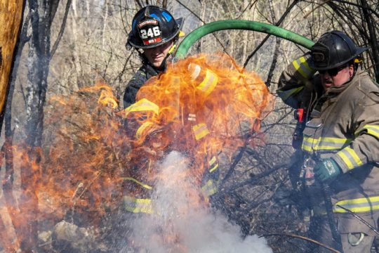 Niskayuna Fire District 1 firefighter Michael Vinehout is assisted by Schenectady firefighter Lt. Daniel Minersagen in putting out a pile of burning tires behind the Jewish Community Center Saturday
