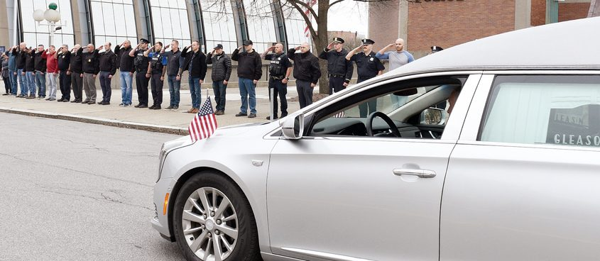 Local law enforcement and first responders stand in formation outside the police station as they honor Retired Schenectady Police Sgt. Ray Wemple Monday