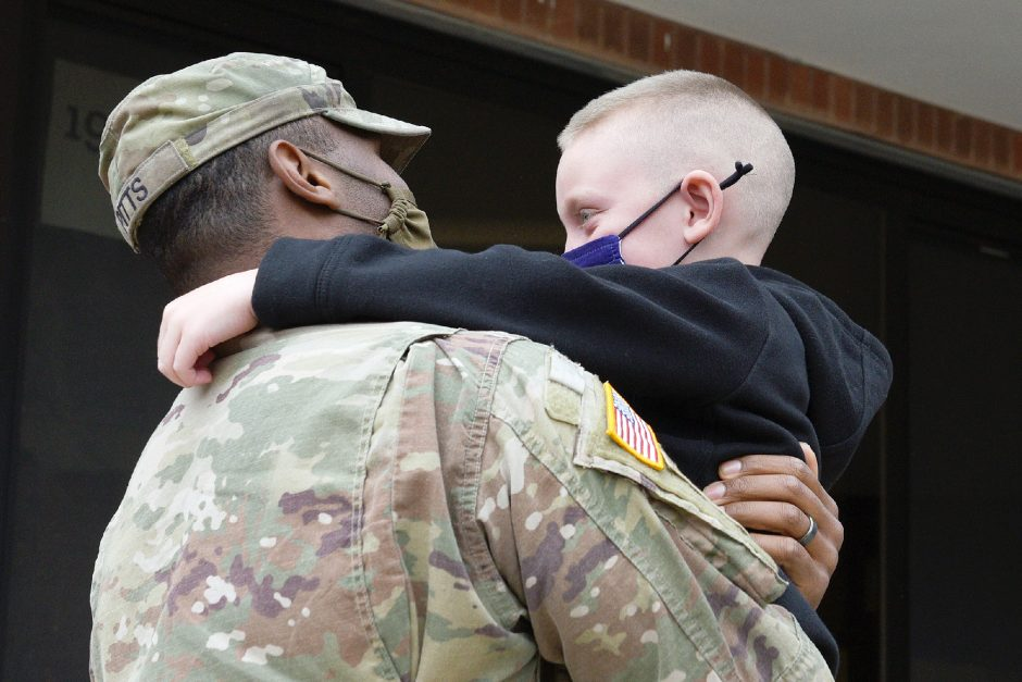 Army Sgt. Derrick Pitts hugs his stepson Camden Wade, 7, outside the entrance of William H Barkley Elementary in Amsterdam on Friday. Pittts arrived Friday morning after serving 11 months in Iraq, Afghanistan and Kuwait.