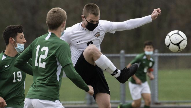 Nathan Carter of Mohonasen clears the ball in front of Schalmont's Dan Tommasone, right, and Paulie Brosious during Saturday's Colonial Council boys' soccer game at Schalmont High School