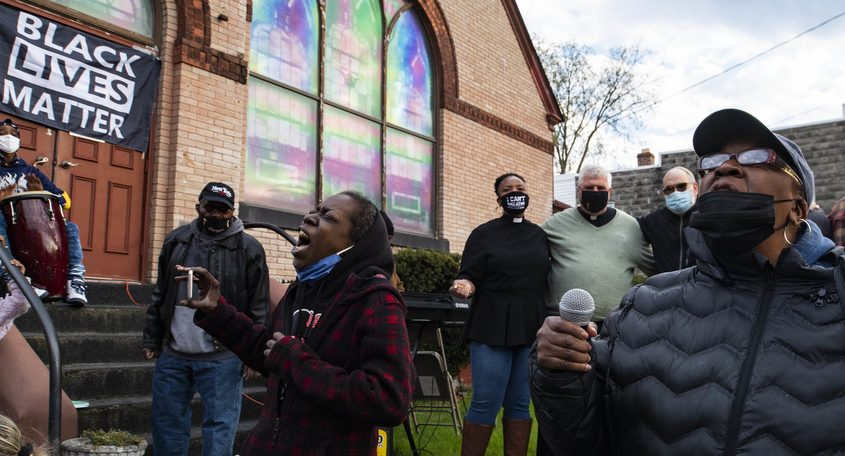 Larissa Tucker, left, and Cheryle Lindsay sing 'We Shall Overcome' at the closing of a vigil in front of the Duryee Memorial AME Zion Church on Hulett Street Tuesday