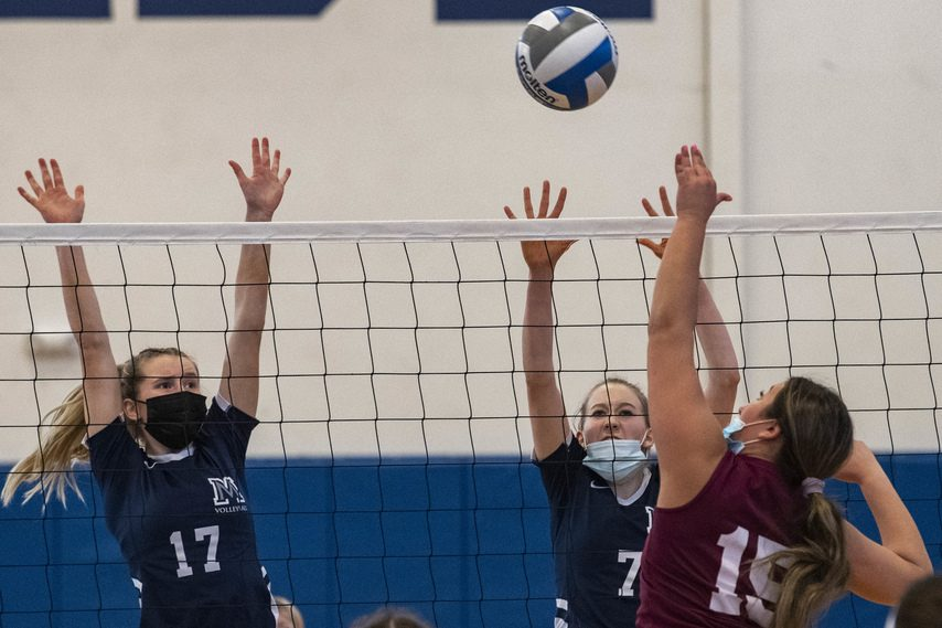 Mekeel Christian Academy's Hanah Graham-Parker, left, and Rose Seredensky try to block a shot by Notre Dame-Bishop Gibbons' Juliana Tortello during Tuesday's Western Athletic Conference volleyball match at Mekeel.