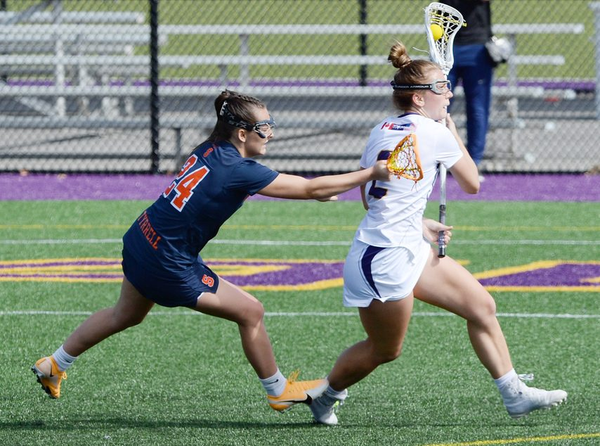 UAlbany's Kendra Harbinger with the ball against Syracuse's Emma Tyrrell duringan April 13 game in Albany.