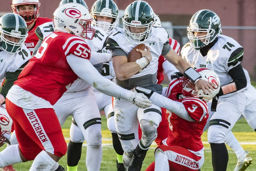 Shenendehowa quarterback Brody Vincenzi is wrapped up by Guilderland's Paris Hart, left, and Marcus McClaine on Friday at Guilderland High School.