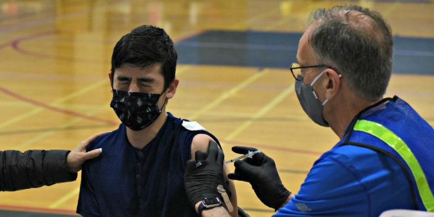 Alvaro Vigil, 17, a SchenectadyHigh School sophomore, winces just a little after getting his Pfizer COVID-19 vaccination from pharmacist Steve Smith at Sunday's vaccination clinic atthe school.