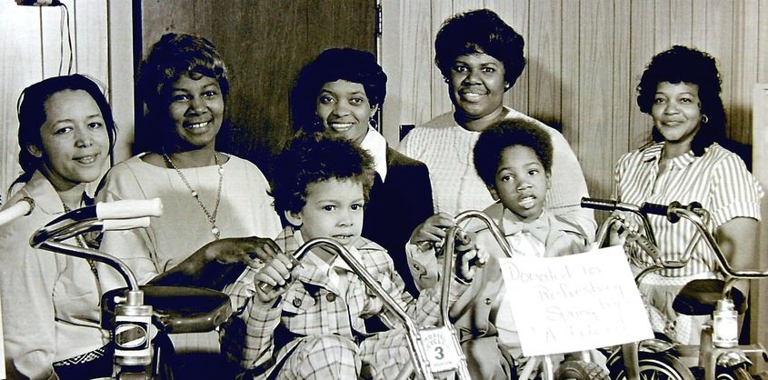 Tots and tricycles were part of the third annual dinner meeting of Refreshing Spring Day Care Center in April 1975. From the left, in back, are Bess Haile, Georgetta Dix (then executive director of the center), Joanne McNeal, Ann Pettress and Nellie Jackson. Ready to ride are Mark Dix, left, and Michael Grandison.