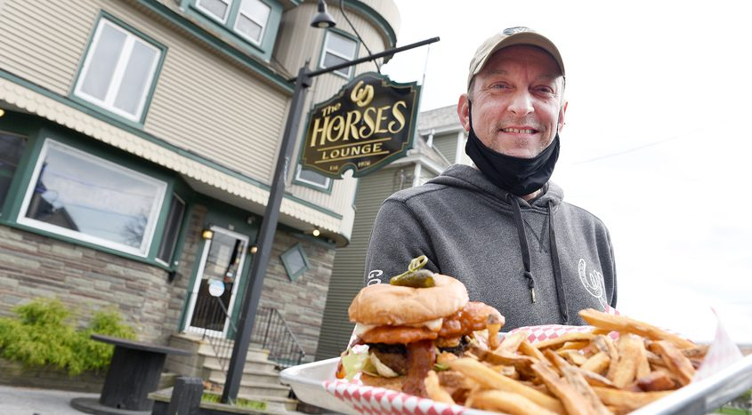 """Owner of The Horses Lounge Christian """"Lil Fred"""" Fritzen holds his Clydesdale Clucker outside their restaurant in Schenectady."""
