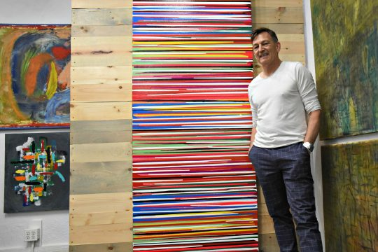 "Joey Matula, owner of Electric City Art Gallery on Jay Street in Schenectady, stands next to ""Scan,""one of his modern art paintings."