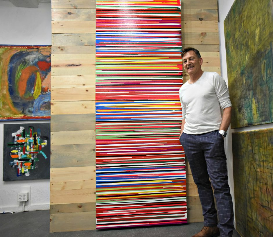 """Joey Matula, owner of Electric City Art Gallery on Jay Street in Schenectady, stands next to """"Scan,""""one of his modern art paintings."""