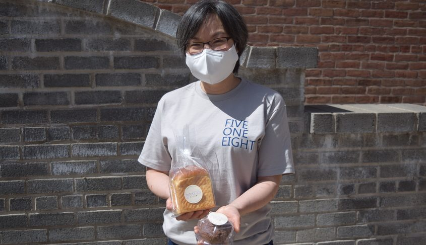 Sookyung Lee, founder of Ppang Bakery, holds a loaf of milk bread and one peanut butter & chocolate cookie bread.