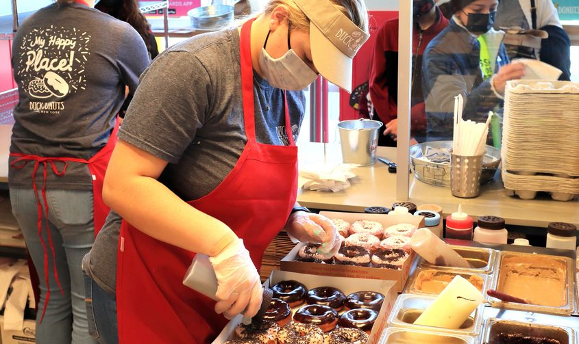 Duck Donuts employee Madalynn Walsh decorates two dozen donuts at the Latham shop