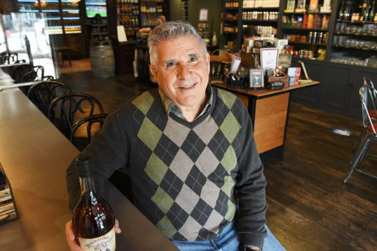 Founder and owner Eugene Marra, of Cooperstown, sits with their Saratoga Revolutionary Rum at Cooperstown Distillery Beverage Exchange on Broadway in Saratoga Springs