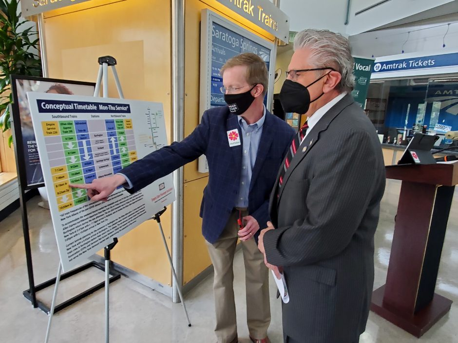 Saratoga County Chamber of Commerce President Todd Shimkus explains the Saratoga Springs passenger rail schedule to state Sen. James Tedisco, R-Glenville, at the Saratoga Amtrak station on Friday.