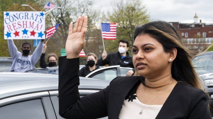 Reshma Ragoobeer takes the Oath of Allegiance with her co-workers behind her at a naturalization ceremony at SUNY Schenectady Friday.
