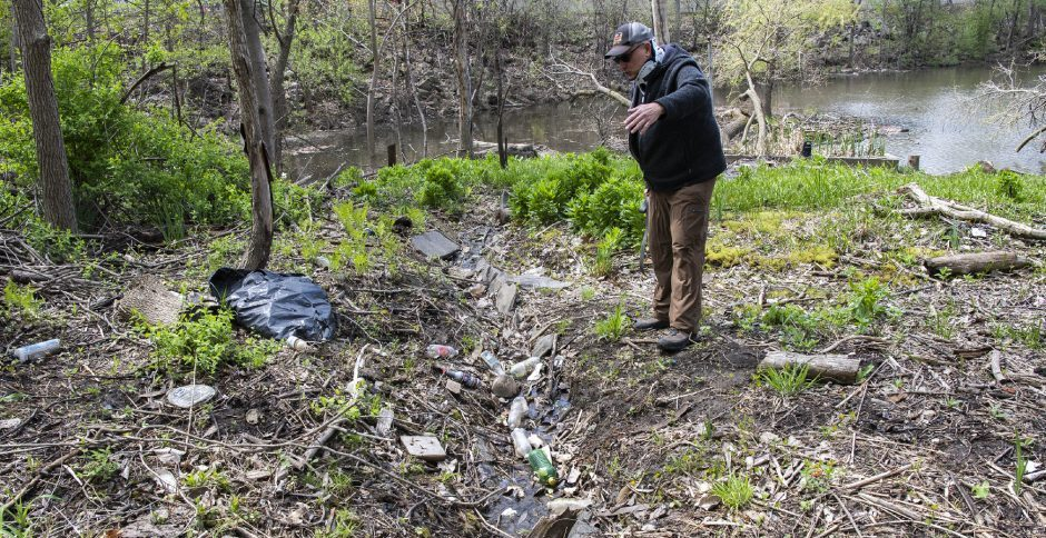 Pete Pasternak shows an area of the Binnekill off the Mohawk River in the Stockade littered with trash and debris on Friday