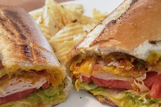 ASmokey Bob sandwich consisting of smoked turkey, melted cheddar, bacon, honey mustard, lettuce and tomato at Genoa Importing.