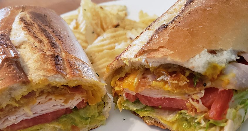 A Smokey Bob sandwich consisting of smoked turkey, melted cheddar, bacon, honey mustard, lettuce and tomato at Genoa Importing.