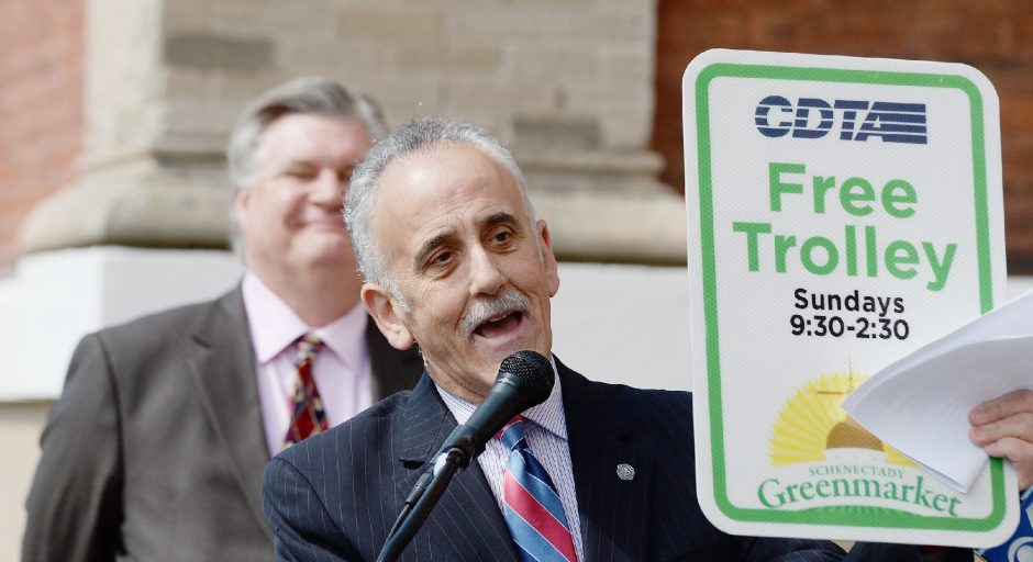 Capital District Transportation Authority CEO Carm Basile holds a sign for the free trolley to the Schenectady Greenmarket, which is held downtown, while discussing the new program on Thursday.