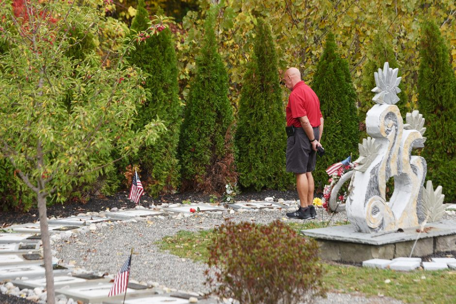 A man walks around the memorial site of the deadly Schoharie limousine crash at the intersection of routes 30 and 30A in Schoharie on Sept. 29.