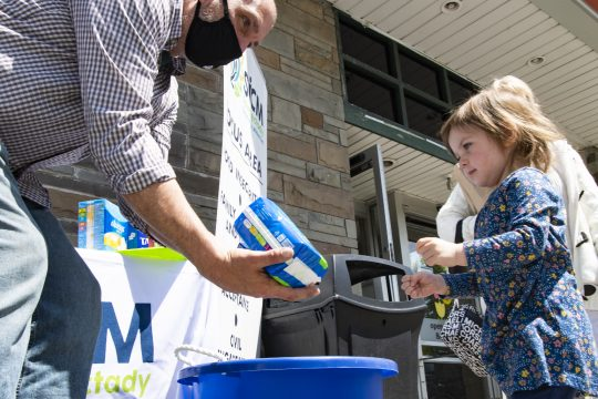Two-year-old Ave Cremo, right, hands Tom Schofield of SICM some women's health care products in front of the Niskayuna Co-opon Friday.