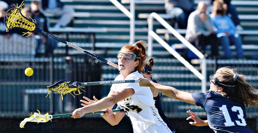 In between two Monmouth defenders, Siena's Kaitlyn Dowsett fires a shot during Thursday's semifinal in Loudonville.