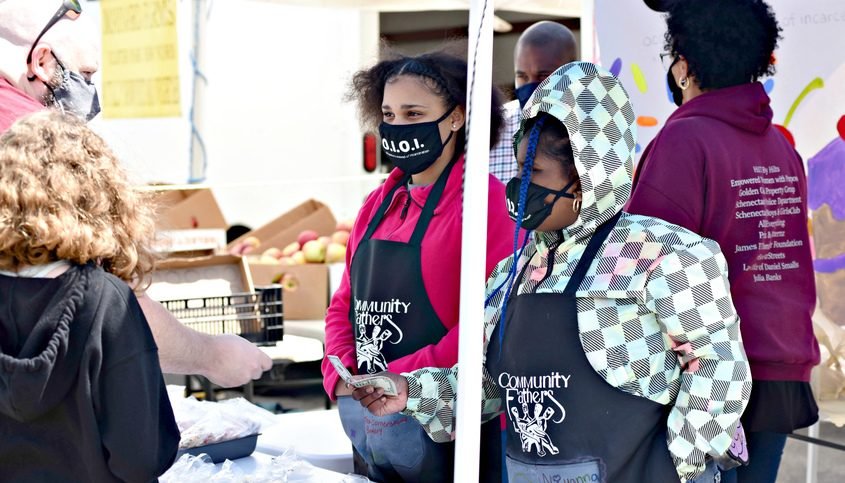 Aniyah Wright, 13, left and Niyanna Brooks, 8, both of Schenectady, talk to a customer at the at the Cornerstone Bakery tent at the SchenectadyGreenmarket Sunday.