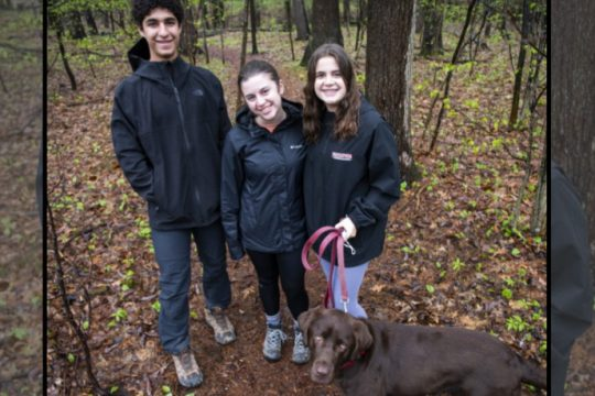 Members of the Niskayuna High School Outing Club, from left, Michael Piccioni, Alex Gallo and Gianna Gallo, and Sherman, pause during their hike at the Henry Gerber Reist Bird Sanctuary off St. Davids Lane in Niskayuna.