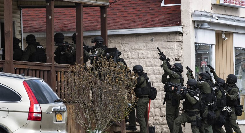 Members of the Schenectady police Special Operations Squad enter a home on Becker Street Monday