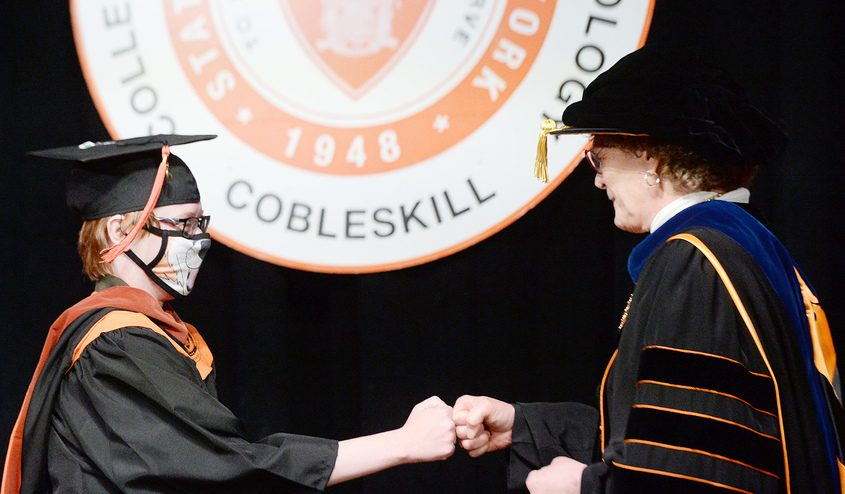SUNY Cobleskill president Marion Terenzio fist bumps with a graduate after handing out a diploma Tuesday