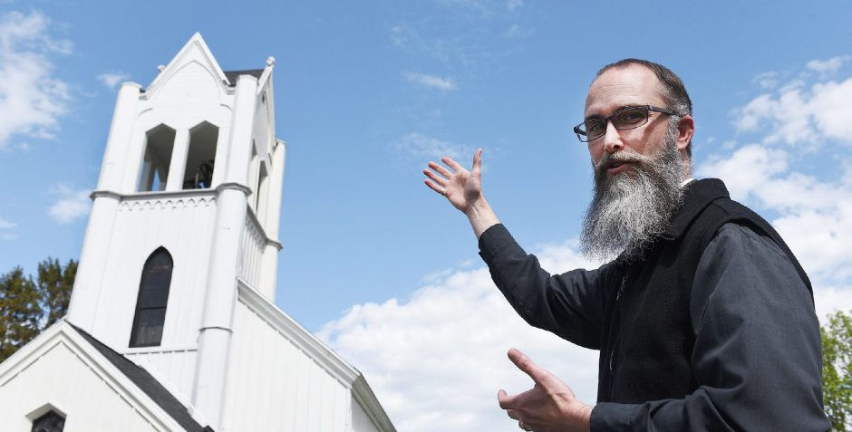 Father Gabriel Morrow points to the top of the Calvary Episcopal Church in Burnt Hills.