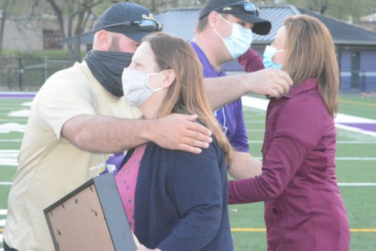 Amsterdam/Broadalbin-Perth boys' lacrosse coach James Natole, left, hugs Debbie Lansburg as she is presented with a commemorative No. 18 jersey in honor of her son, Pete Lansburg, who died in 2001. A ceremony honoring Pete Lansburg's memory was held during halftime of Monday's game against Johnstown at Lynch Literacy Academy.