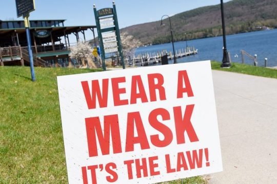 ERICA MILLER/STAFF PHOTOGRAPHER Sign of the times: A sign greetsvisitors to Lake George in May 2020. A year later, mask requirements are being dropped for some people in some circumstances.