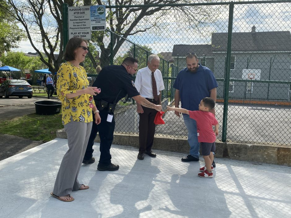 """Gloversville Chief Anthony """"Tony"""" Clay fist bombs a young child Thursday in front of """"The Cage"""" at Elk Street Playground on East Fulton Street while Mayor Vince DeSantis and City Clerk Jenni Mazur stand on each side of him."""