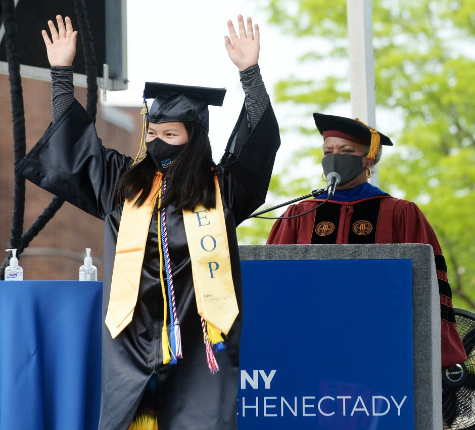 SUNY Schenectady graduate LeeAna Doolin of Berne celebrates as she receives her diploma during the school's outdoor Grad Walk on Thursday.