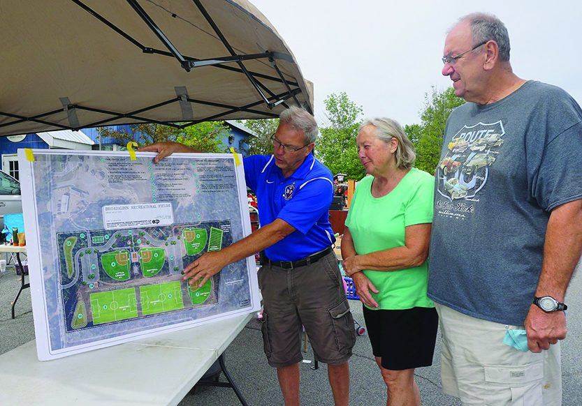 Keith Buchanan shows Pat and Don Halsdorf of Mayfield the layout of the town park at a fundraiser event in 2017. (File photo)