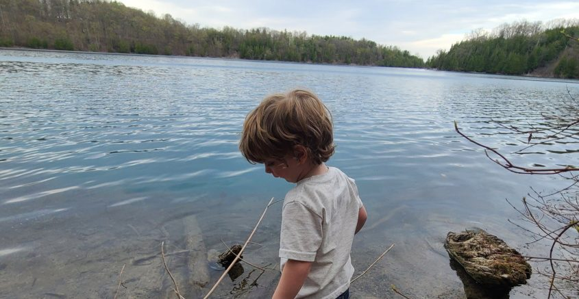 Brody Shivers of Syracuse explores the shoreline of Green Lake in Onondaga County. Below: A fisherman tries his luck on Onondaga Lake.