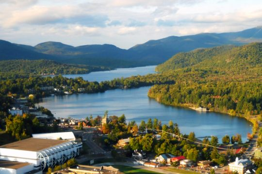 An overhead view of the village of Lake Placid shows the Olympic Center (foreground) , Mirror Lake and, in the distance, Lake Placid and Whiteface Mountain.