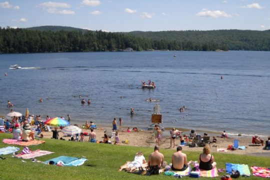 The sand — and grass — at the Schroon Lake town beach are crowded during a summer day.