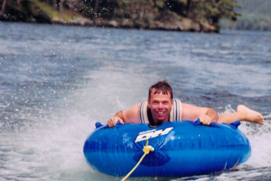 The writer's husband, Scott, is all smiles after doing a 360 flip while tubing on Lake George.