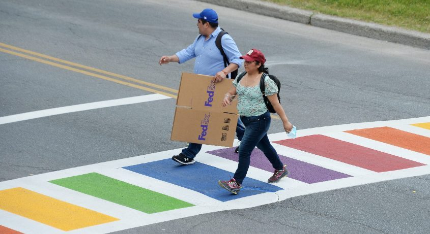 People cross Spring Street to Congress Park on a new rainbow-colored crosswalk, representing LGBTQ pride colors, in Saratoga Springs on Wednesday.